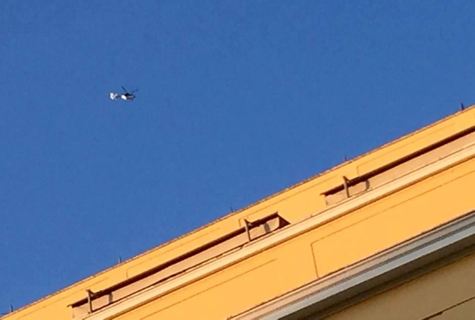 Un hélicoptère de police tourne autour de nous, au-dessus des bâtiments.